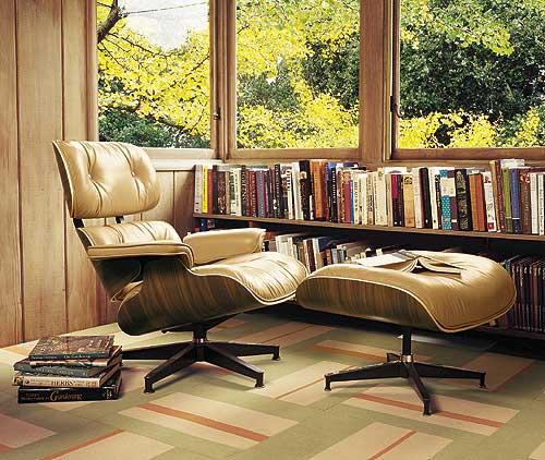Cadeira Eames em tom marrom claro, na decoração de uma biblioteca doméstica aconchegante