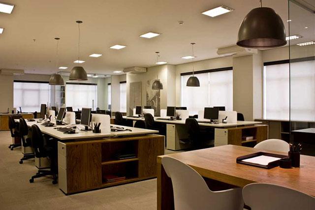 Mesas de um grande escritório voltadas para a janela para aproveitar melhor a luminosidade natural do ambiente