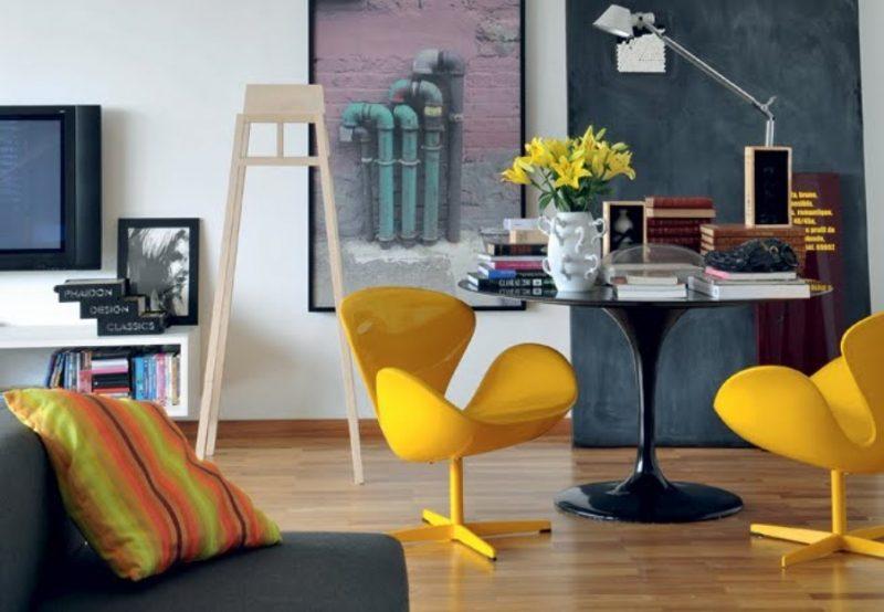 Duas poltronas swan amarela laqueadas completam o conjunto com uma mesinha redonda preta