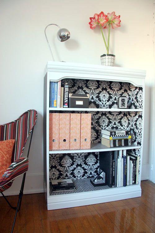 Estante para a sala recebe uma pintura branca e revestimento no interior com papel de parede preto e branco