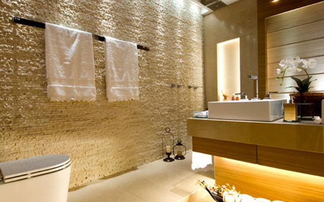 Revestimento da parede do banheiro fica por conta da pedra São Tomé filetada - ou revestimento canjiquinha - dando um efeito muito mais natural à parede.
