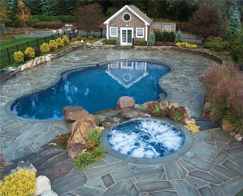 Piscina em casa pequena europeia com hidromassagem e piscina em formato bem arredondado