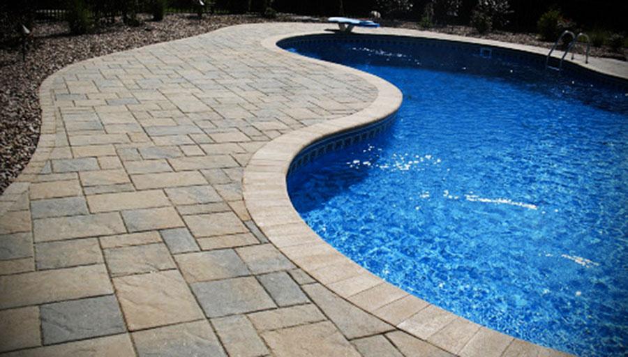 Já nessa piscina, usa-se lajotas antiderrapantes para o piso do entorno