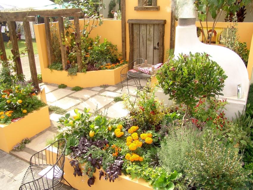 Neste jardim tipo mediterrâneo, as cores das paredes combinam com a vegetação utilizada