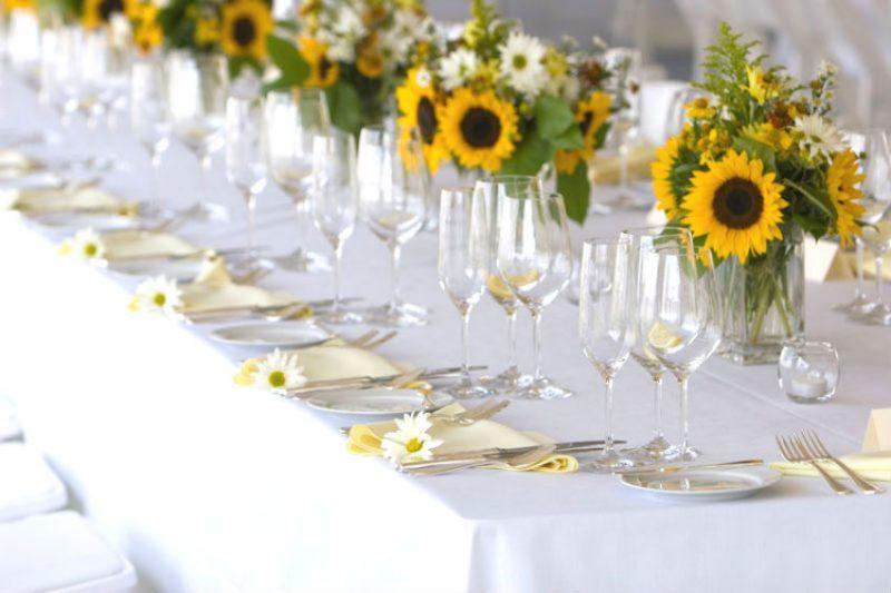Um belo exemplo de decoração de flores em festa - arranjos de girassol enfeitam as mesas e criam pendentes muito bonitos