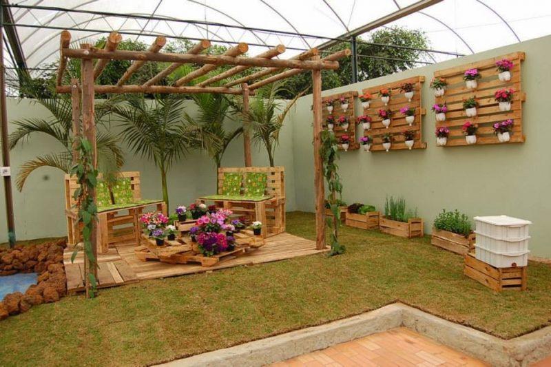 Neste modelo de paisagismo, um pergolado de madeira roliça é decorado com bancos feitos de paletes e caixas de madeira reaproveitados.
