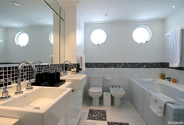 Nesse banheiro, uma faixa e pastilhas adesivas quebra o tom monótono do revestimento branco