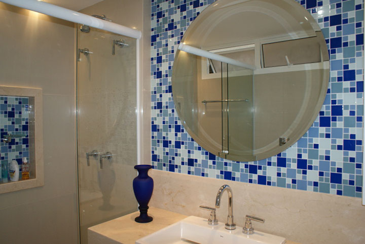 em uma variação da ideia anterior, um painel com pastilhas adesivas azuis atrás do espelho do banheiro