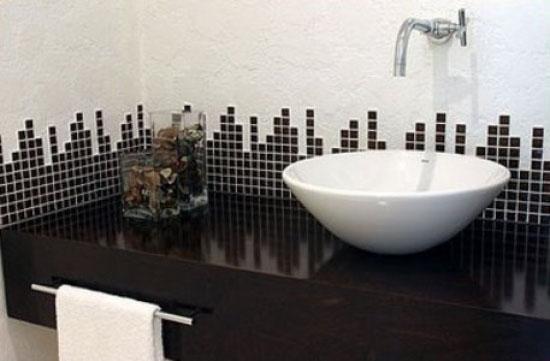 Pastilhas adesivas fazendo um detalhe no revestimento da parede sobre a pia do banheiro