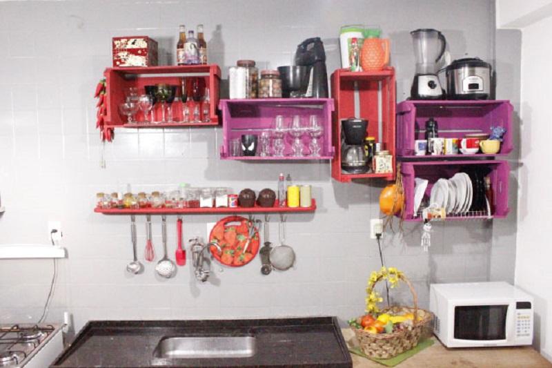 Nessa cozinha, ao invés de se gastar com um armário suspenso, se fixaram na parede caixas de madeira pintadas, o que deu um resultado super descolado