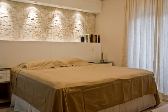 Já nesse quarto, o revestimento serve como um detalhe decorativo para a parede sobre a cama de casal