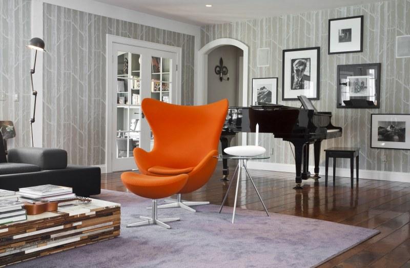 Já nessa sala, a cadeira assume uma posição de destaque, com uma cor forte, que se destaca do fundo cinza