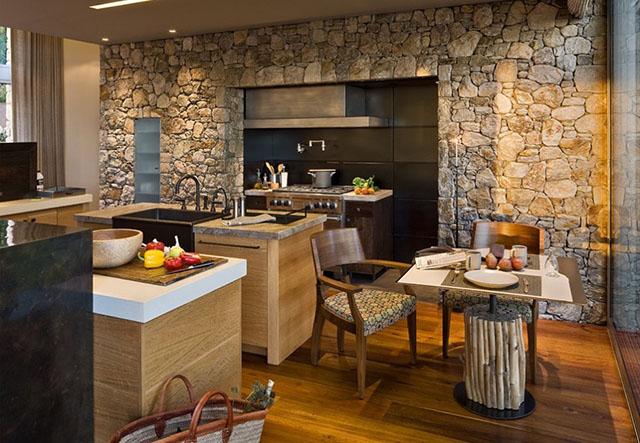 A parede revestida em pedra contrasta com o visual super moderno desta cozinha