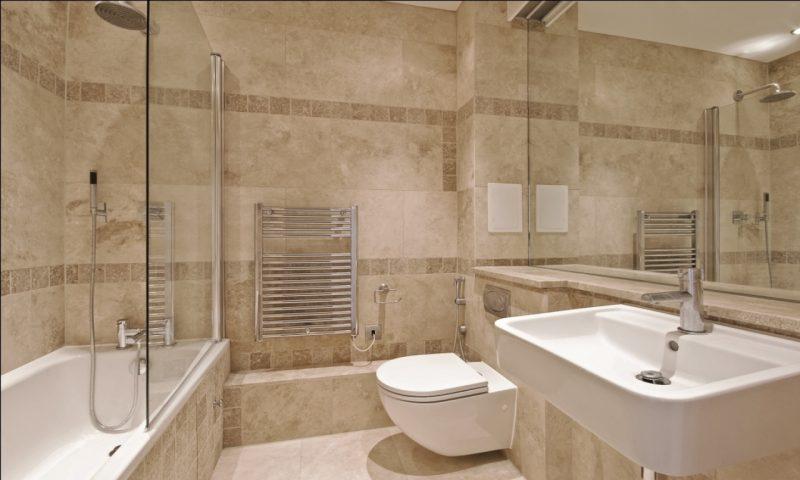 Revestimento do banheiro em mármore travertino, decorado com faixas de granito