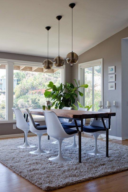 bela mesa de jantar posta rodeada por cadeiras tulipa brancas com assento azul