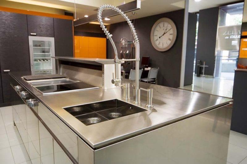 Bancada de pia de cozinha em aço escovado, reforçando o toque moderno desse ambiente