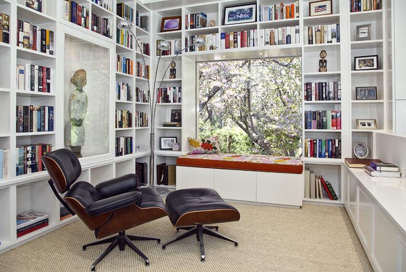 Biblioteca em casa decorada com a poltrona Eames
