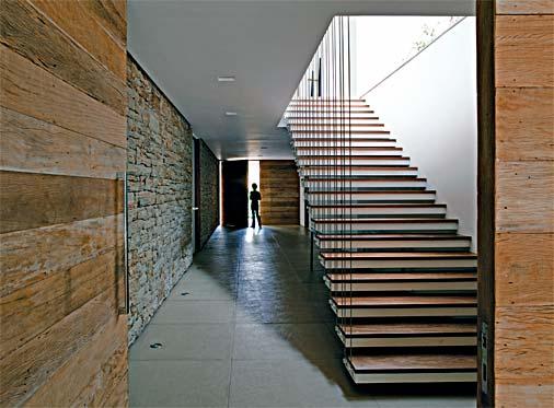 Revestimento de corredor interno em segundo plano, feito com pedra madeira