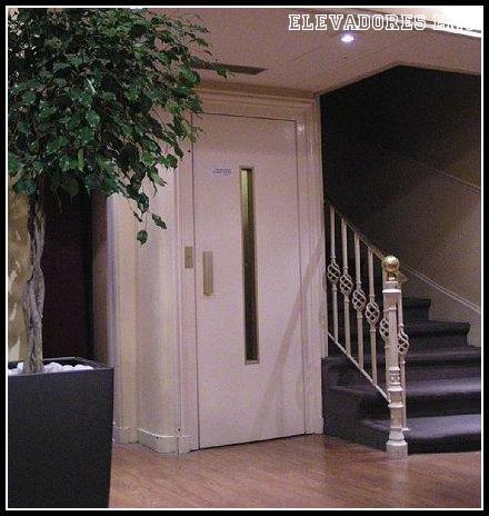 Modelo de elevador de contrapeso em ambiente residencial ao lado de escada de madeira
