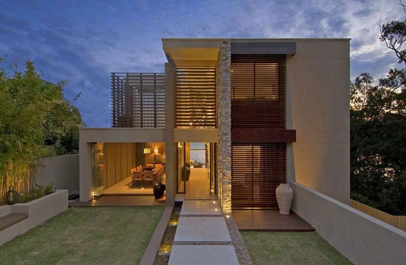 Elemento vertical na fachada de casa moderna revestido em pedra madeira