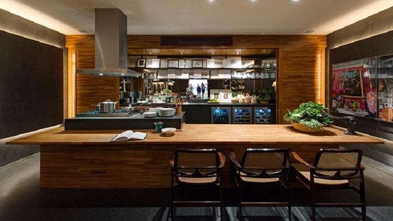 Cozinha revestida com madeira filetada, mostrando como esse revestimento combina bem com a decoração contemporânea