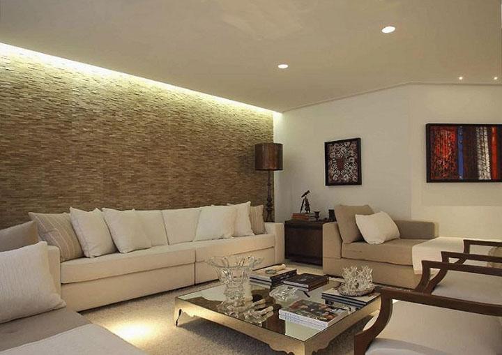 Já essa sala de estar usa uma parede inteira revestida com madeira filetada clara