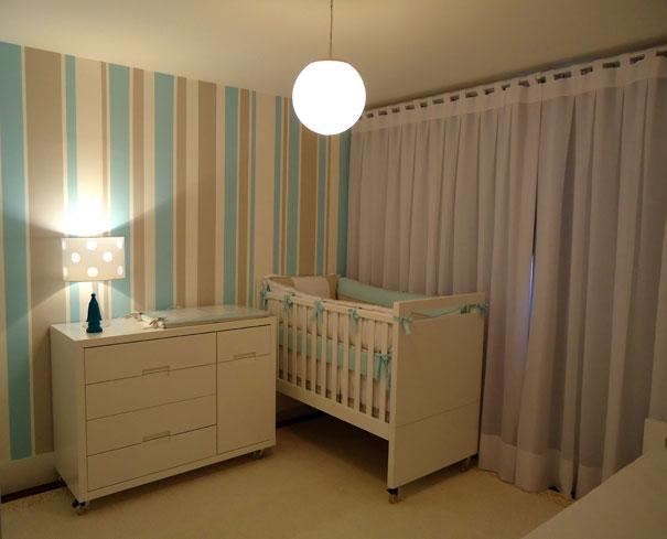 Parede listrada em quarto de bebê masculino com listras verticais de azul e cores intercaladas