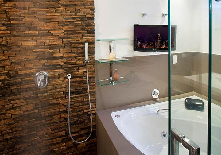 Parede de banheiro revestida com filetes de pedra ferro
