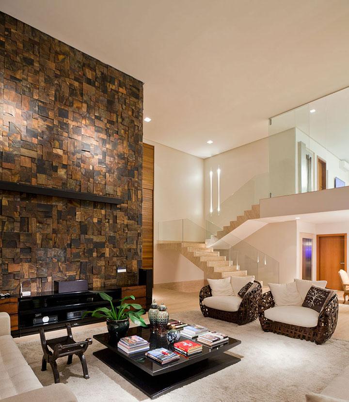 Parede de sala de estar com pé direito duplo revestida com pedra ferro