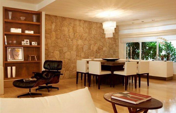 Nessa sala, a parede de Pedra madeira acompanhada do Lustre e da Poltrona Eames dão um toque mais retrô ao ambiente