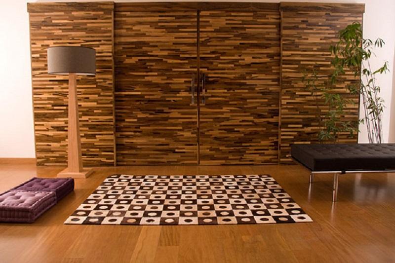 Parede da sala de estar revestida com madeira filetada e piso com tábuas de madeira maciça
