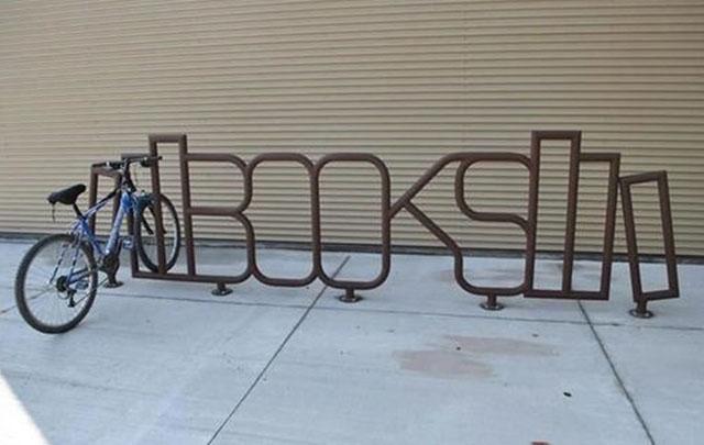 Esse bicicletário em aço cortem faz propaganda da livraria na calçada