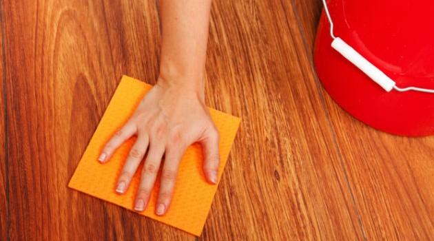 uso de um pano com solução para limpeza do piso laminado