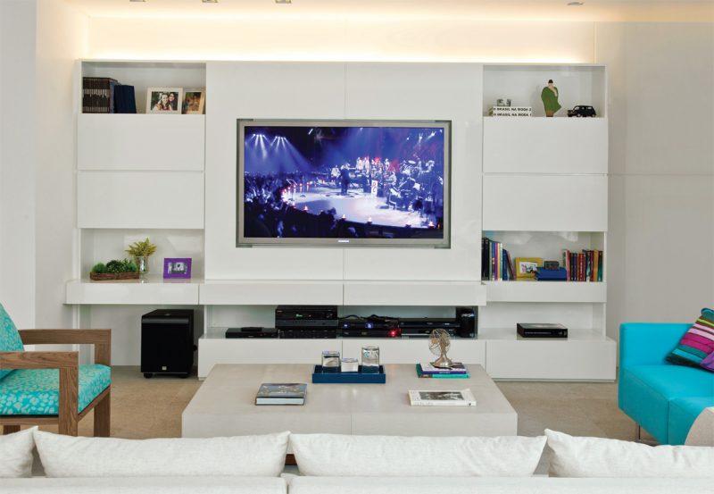 Já essa decoração de home theater aposta no branco dos móveis, com mesa de centro baixa próxima ao sofá