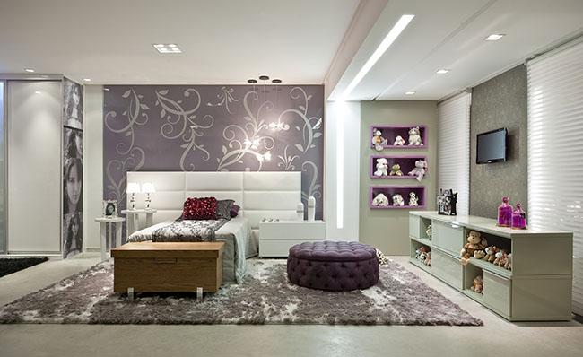 Esse modelo de quarto usa cores claras, prateleiras para guardar objetos e um tapete felpudo combinando co a cor das paredes