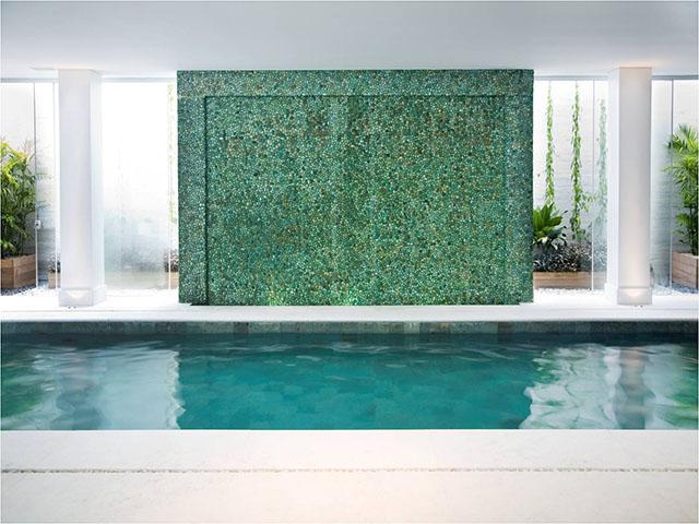 Seixos verdes telados revestindo parede de ambiente de piscina interna