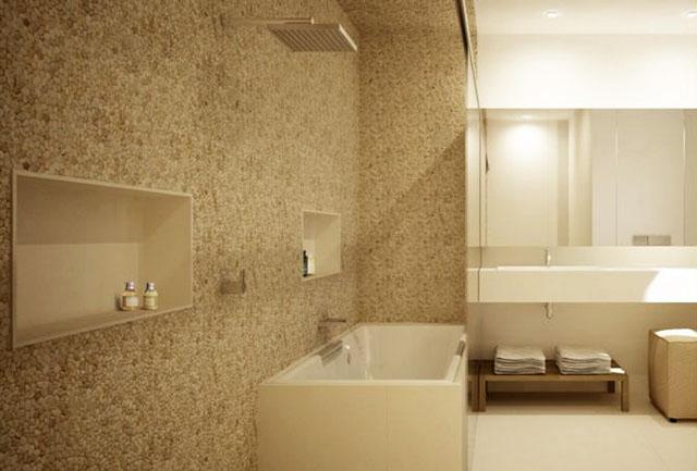 Esse banheiro usa seixos com tom bem claro para o revestimento de parede