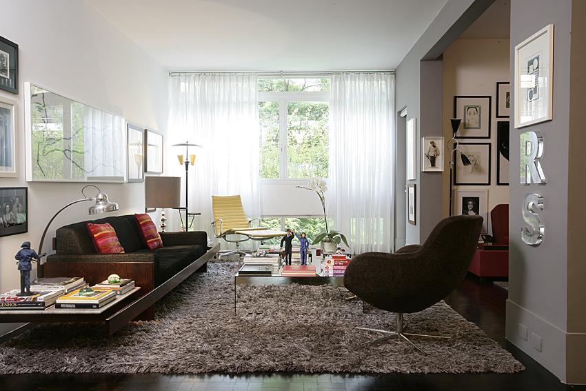 Já essa sala mantém o ar mais sóbrio com uso de tapete felpudo com cor escura