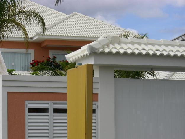 Telhado 4 águas na casa e em portão eletrônico feito com cobertura colonial pintada em branco
