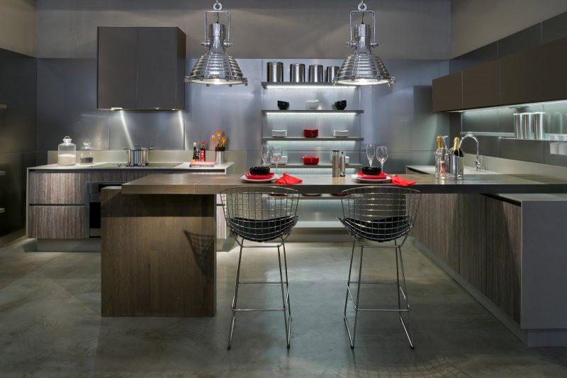 O uso do inox pode ocorrer pontualmente, como nessa cozinha, em que é usado nas luminárias, banquetas e alguns elementos decorativos