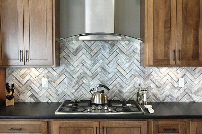 Partilhas em inox da cozinha que lembram a textura do piso parquet