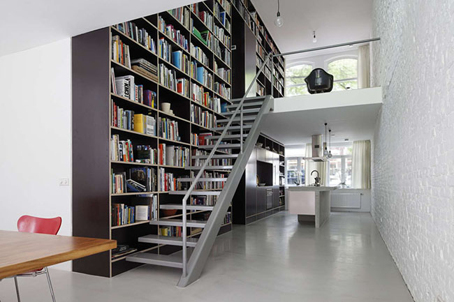 Parede de sala preenchida com estante de grandes proporções para biblioteca pessoal em casa.