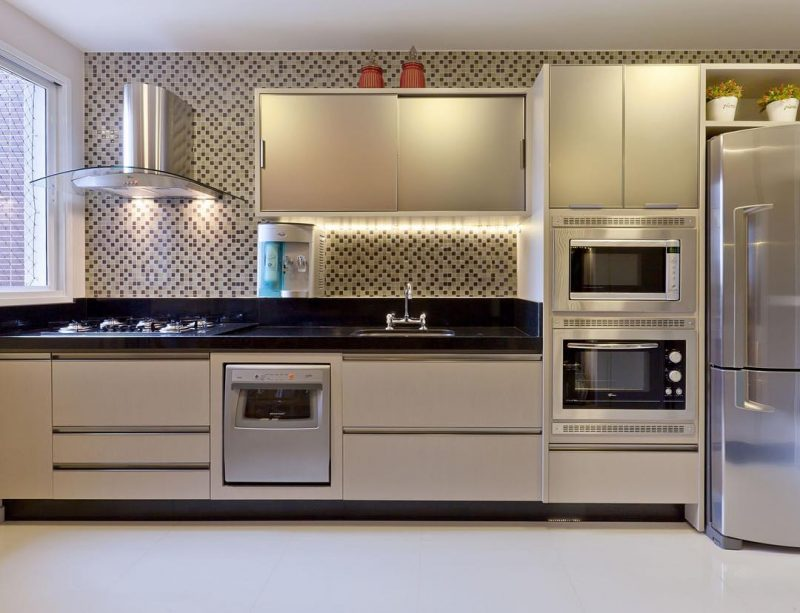 Cozinha decorada com pastilhas de aço inox, combinando com outros elementos em inox