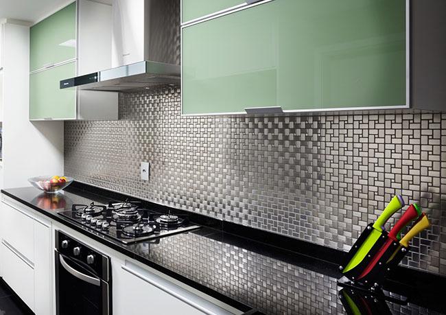 Ao fundo, revestimento de pastilhas em inox cria um efeito singular na decoração de parede de cozinha