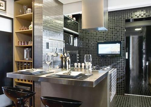 A parede revestida com pastilhas inox combinando com o balcão da cozinha integrada