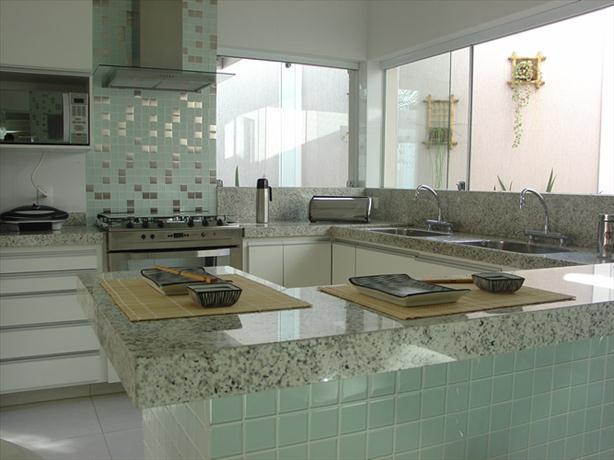Esse ambiente de cozinha decorada mescla o uso de pastilhas de inox com pastilhas de vidro