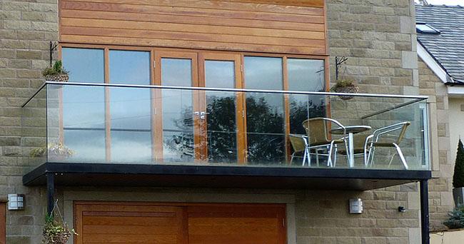 sacada de vidro em casa com fachada de madeira