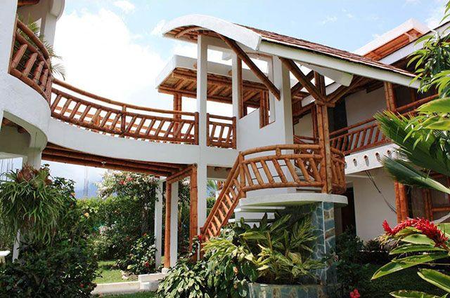 Projeto de casa moderna que usa elementos em bambu como guarda corpos