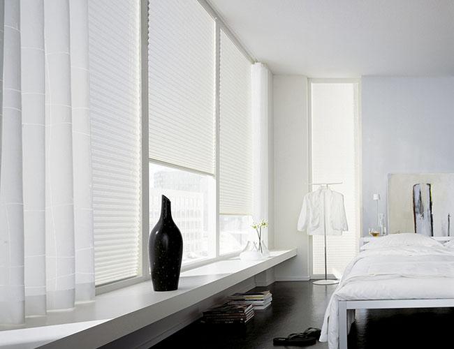 Mesmo os modelos de cortina plissada mais permissivos a entrada de luz são capazes de garantir a privacidade em ambientes como quartos de casal.