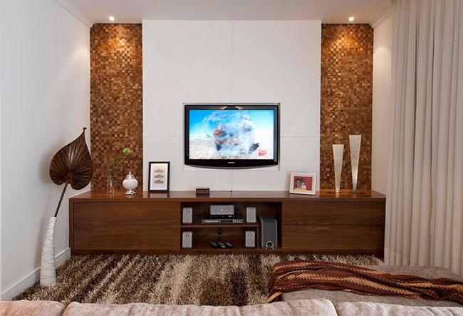 Você pode criar elementos nos revestimentos das paredes que combinem com os móveis para a sala, como esse mosaico de pedras, que combina com o aparador da sala